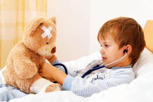 ребенок в постели с медвежонком
