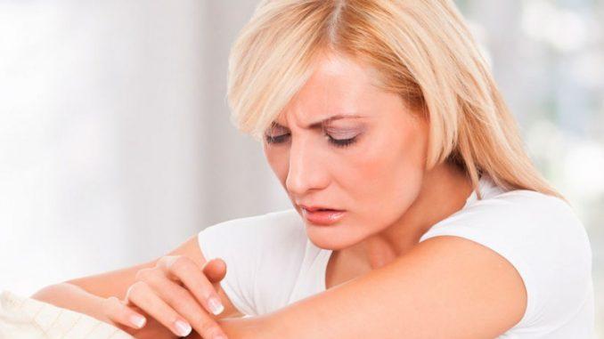 женщина смазывает кремом кожу