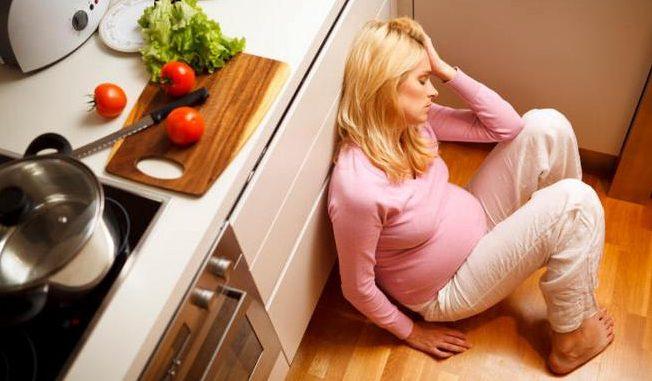 беременная сидит на полу на кухне