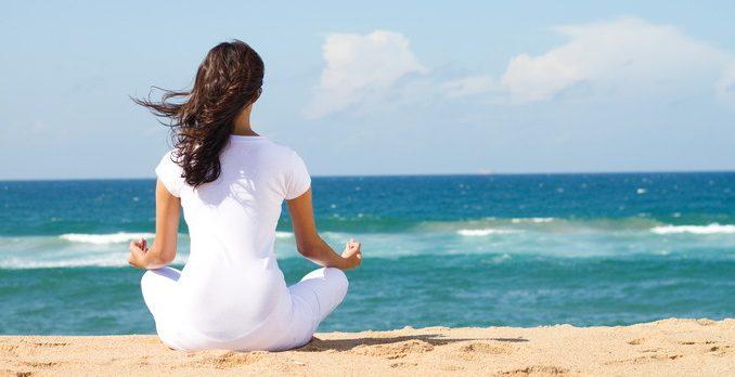девушка медицирует на пляже