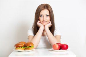 девушка с гамбургерами и яблоками