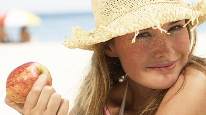 девушка на пляже в панаме с яблоком