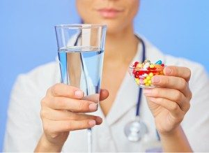 девушка держит стакан воды и таблетки