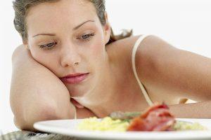 девушка смотрит на тарелку с едой