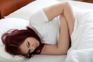 девушка в кровати с болями в животе